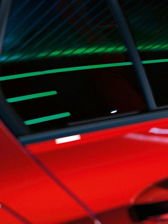 Detalle de la puerta trasera y la ventanilla de un Volkswagen Golf GTI rojo con reflejos de luces de neón