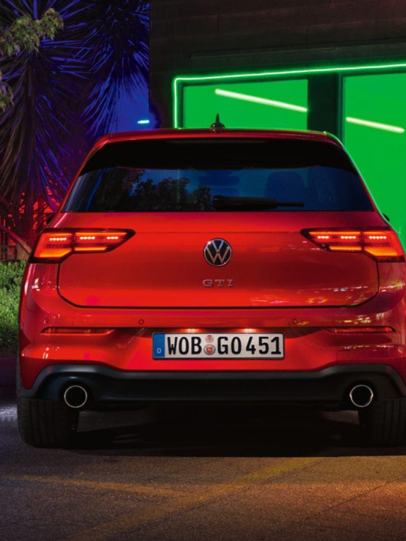 Volkswagen Golf 8 GTI rojo visto desde atrás aparcado de noche frente a una ventana con luz verde