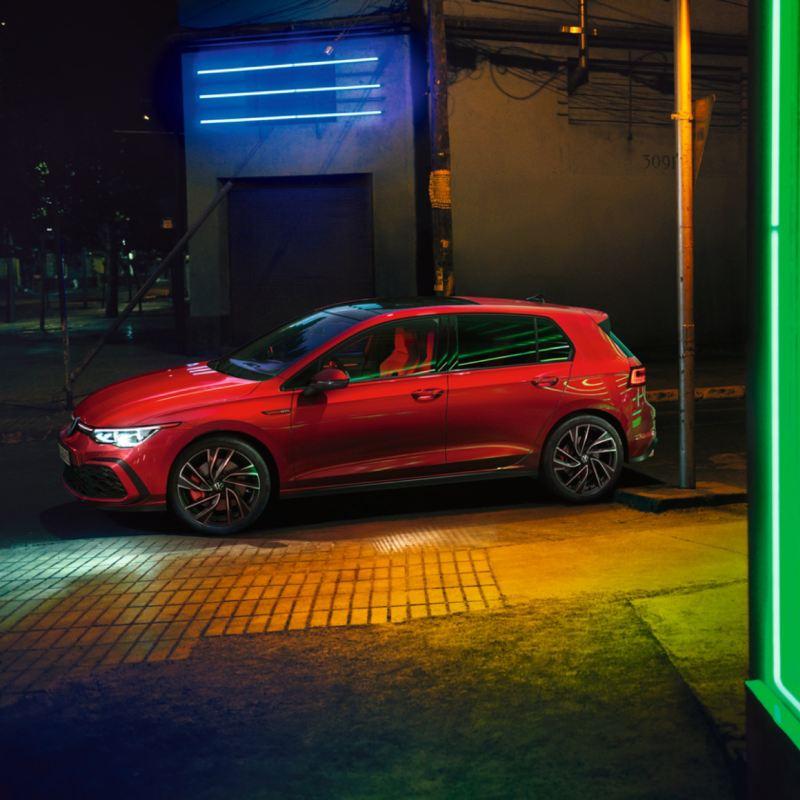 Vista lateral de Golf 8 GTI rojo aparcado en la ciudad de noche
