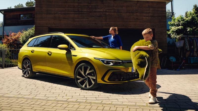 Nuevo Golf Variant amarillo aparcado frente a una casa con una madre al lado y un niño con un peluche delante