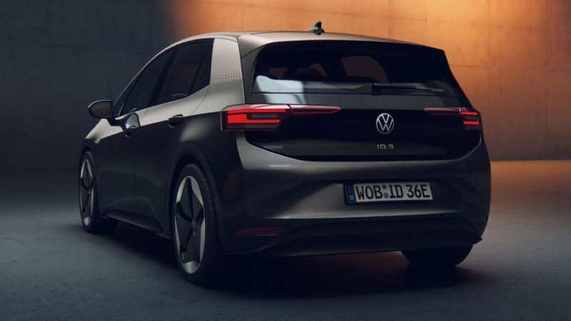 Volkswagen ID.3 negro visto desde atrás aparcado frente a un muro de concreto