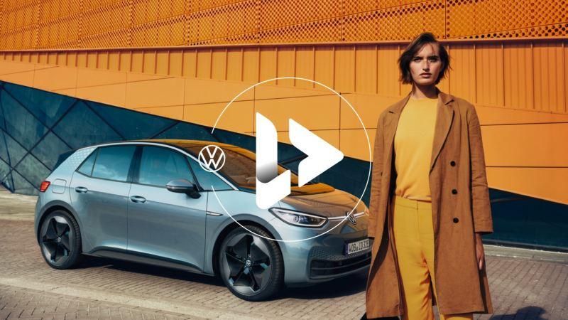 Chica vestida de amarillo delante de un Volkswagen ID.3 aparcado en la calle con un icono de video sobreimpreso