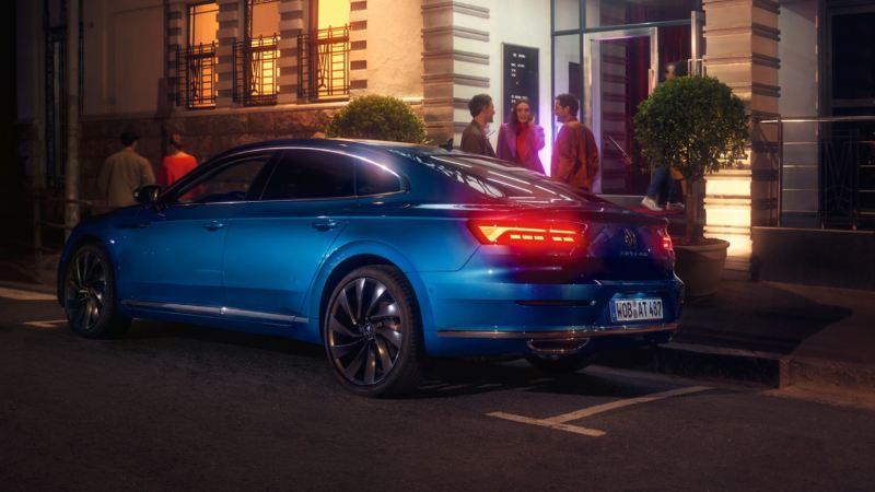 Vista trasera de un Nuevo Volkswagen Arteon azul aparcado en la calle por la noche
