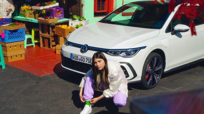 Chica agachada delante de un Volkswagen Golf GTE blanco aparcado