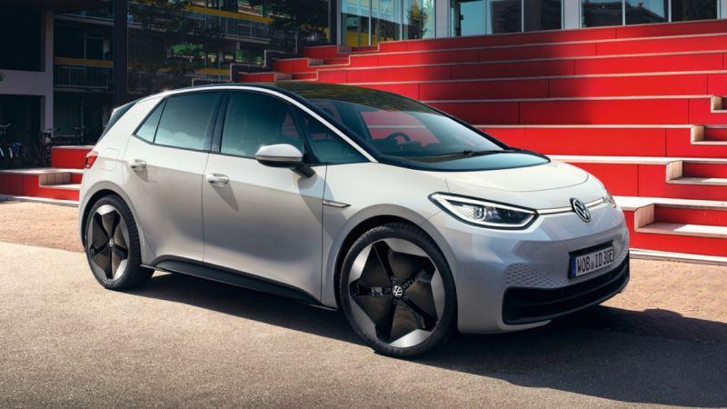 Volkswagen ID.3 blanco visto de costado aparcado delante de unas gradas rojas