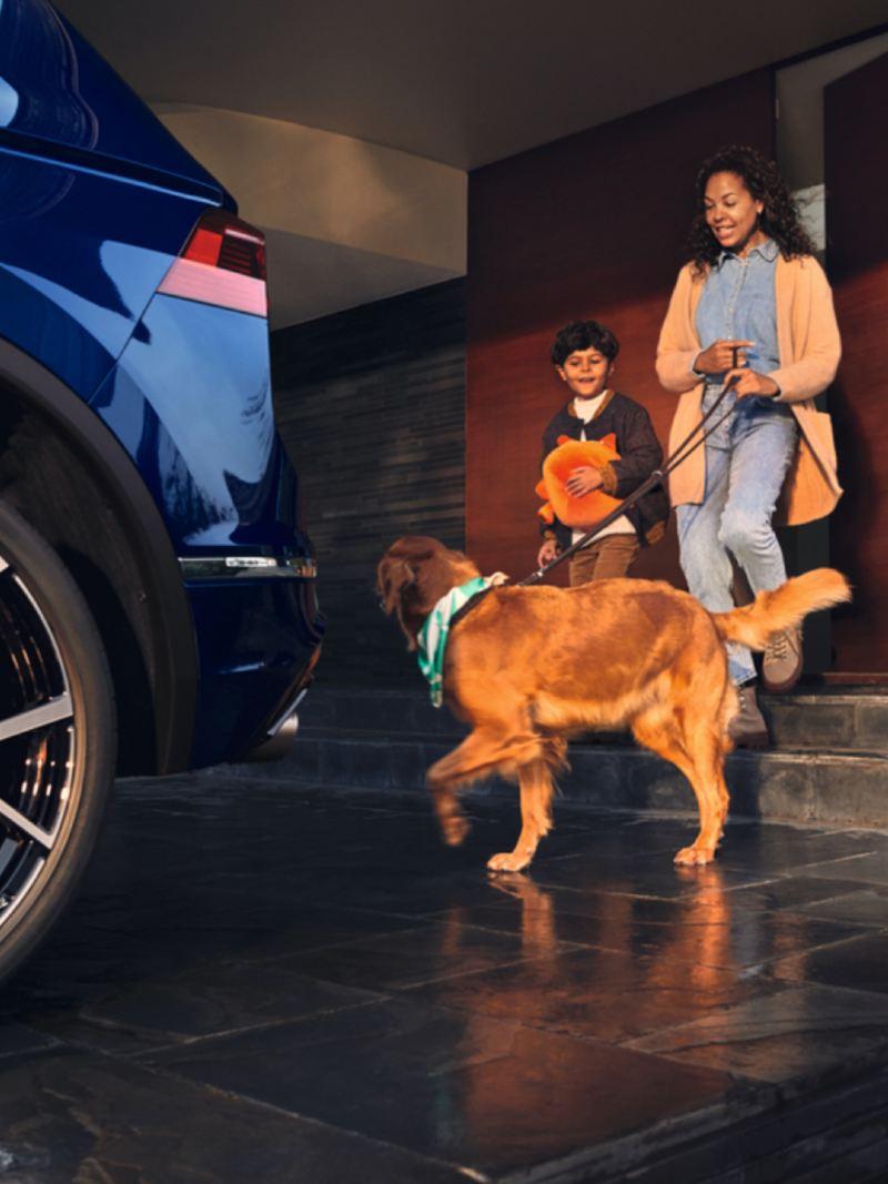 Hombre de pie en primer plano con un Volkswagen Tiguan R azul de fondo aparcado en una nave