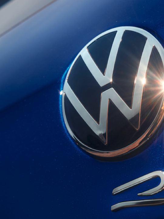 Hombre caminando delante de un Volkswagen Tiguan R aparcado en una nave