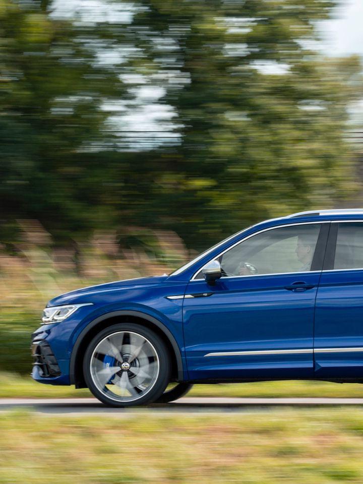Vista lateral de un Volkswagen Tiguan R azul circulando por una carretera