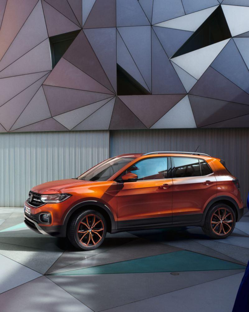 Volkswagen T-Cross color naranja aparcado delante de un fondo con figuras geométricas