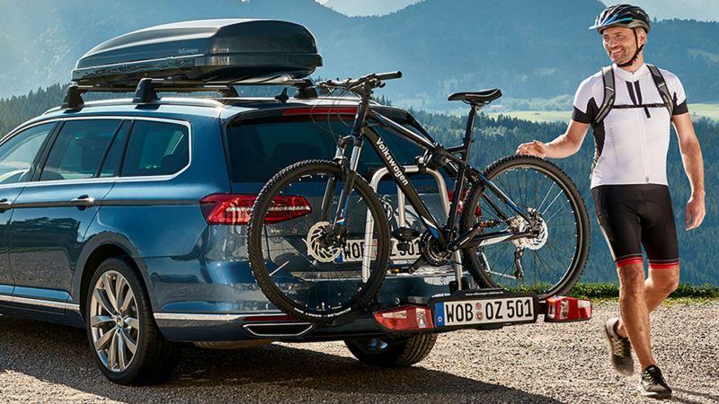 Volkswagen con portabicicleta en la montaña con un hombre joven caminando al costado