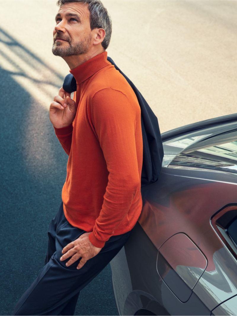 Hombre con un jersey naranja apoyado en la parte trasera de un Arteon R-Line Performance gris