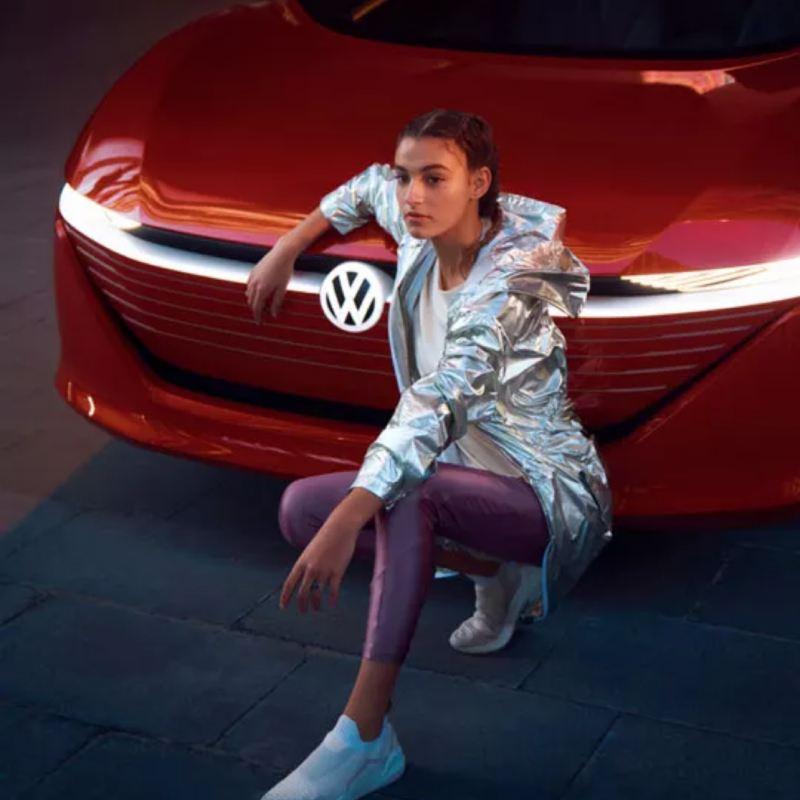 Chica posando de cuclillas apoyada en el frontal de un Volkswagen ID. Vizzion rojo