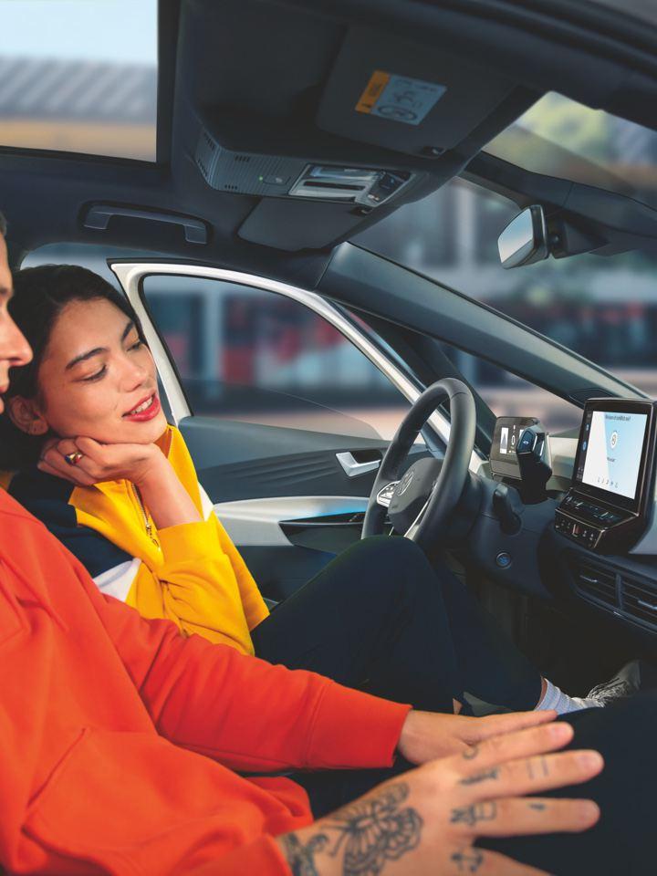 Pareja joven en el interior de un Volkswagen mirando la pantalla del salpicadero