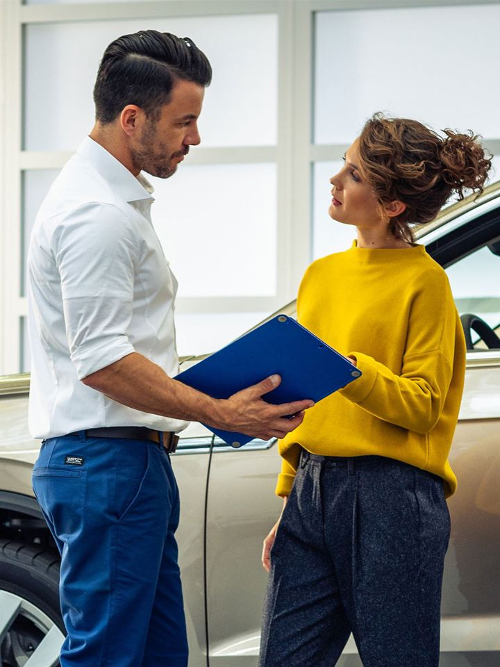 Representante de concesionario con una carpeta hablando con una mujer joven delante de un Volkswagen