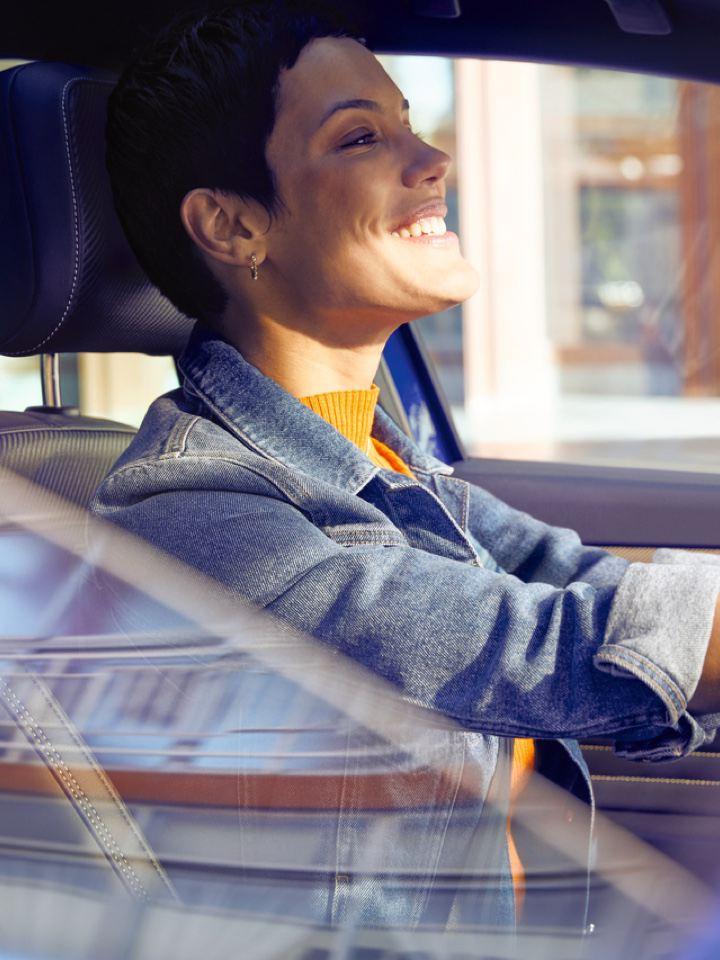 Primer plano de una mujer sonriendo al volante de un Volkswagen