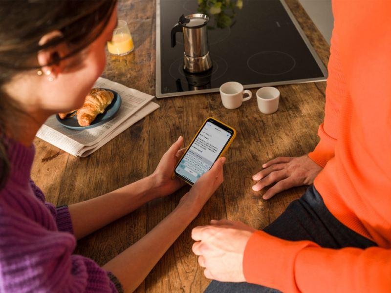 Manos de una chica sosteniendo un teléfono móvil junto a un hombre con un jersey naranja