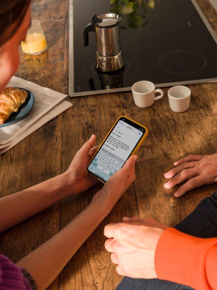 Detalle de una mujer joven usando un móvil sobre una mesa con un hombre sentado al lado visto parcialmente