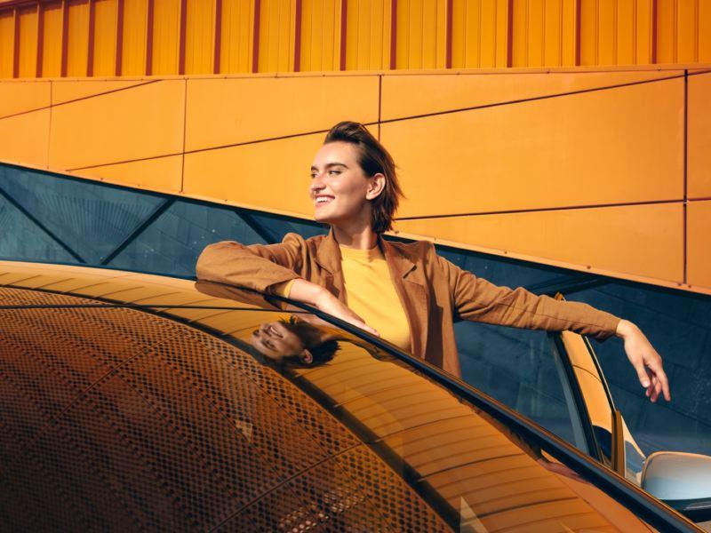 Mujer joven sonriendo apoyada junto a un Volkswagen con la puerta abierta sobre un fondo naranja