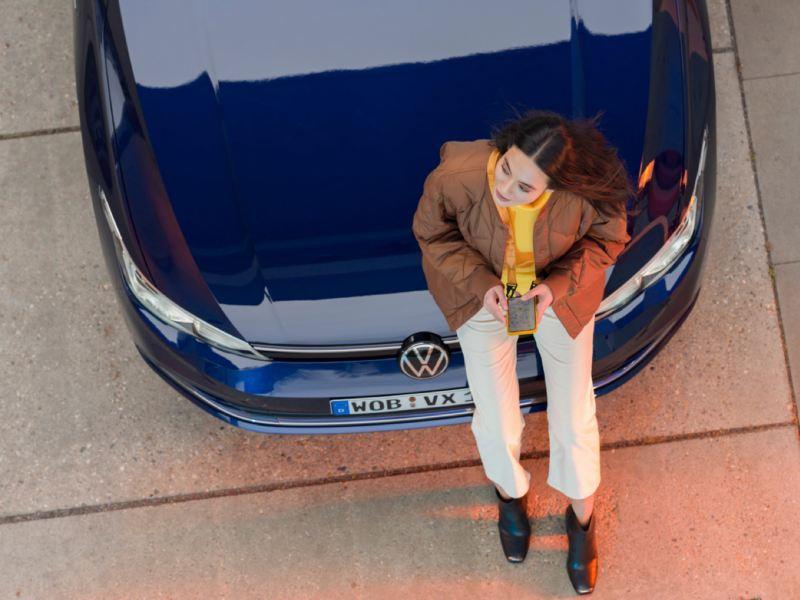 Mujer joven vista desde arriba apoyada en el capó de un Volkswagen usando un móvil