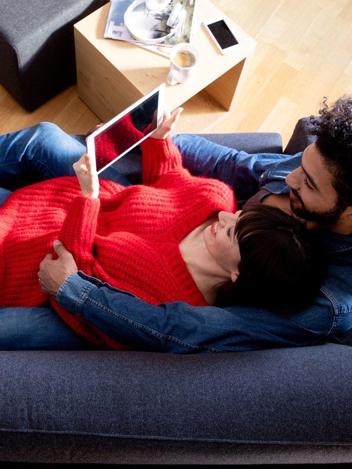 Pareja joven vista desde arriba recostada en un sofá mirando una tablet