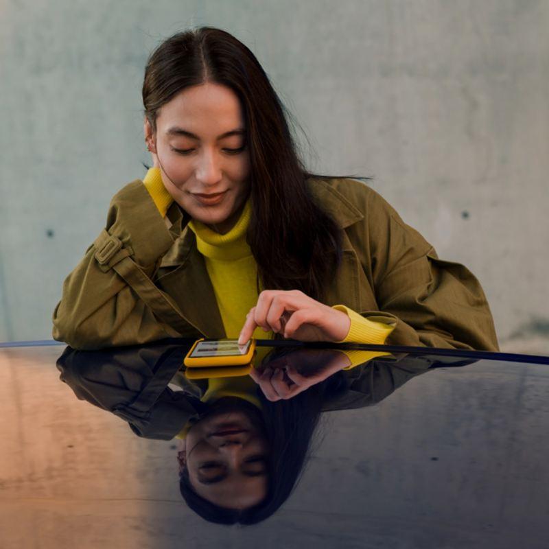 Mujer joven mirando el móvil apoyada en el techo de un Volkswagen