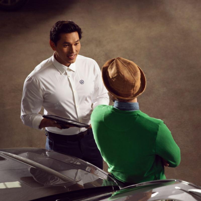 Dos hombres jóvenes hablando apoyados en el capó de un Volkswagen