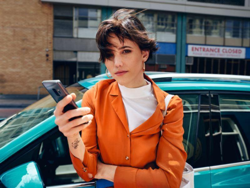 Mujer joven con un teléfono en la mano delante de un Volkswagen turquesa que se ve parcialmente
