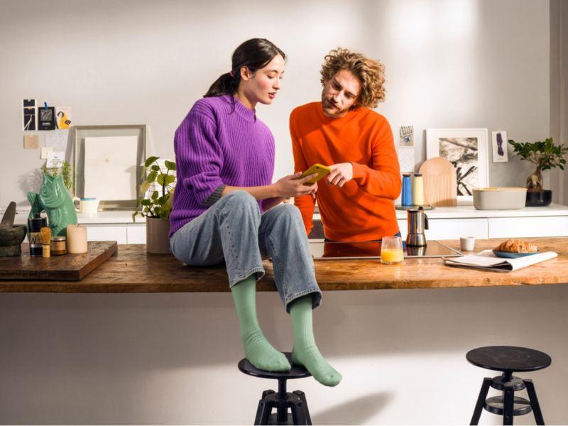 Pareja joven en la barra de una cocina mientras miran un teléfono móvil