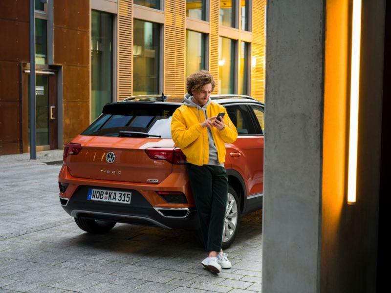 Hombre joven usando un móvil apoyado en un Volkswagen T-Roc visto desde atrás