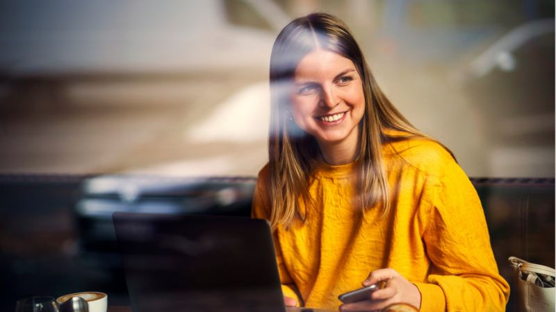 Chica vestida de amarillo sonriendo en una cafetería con un ordenador y un móvil