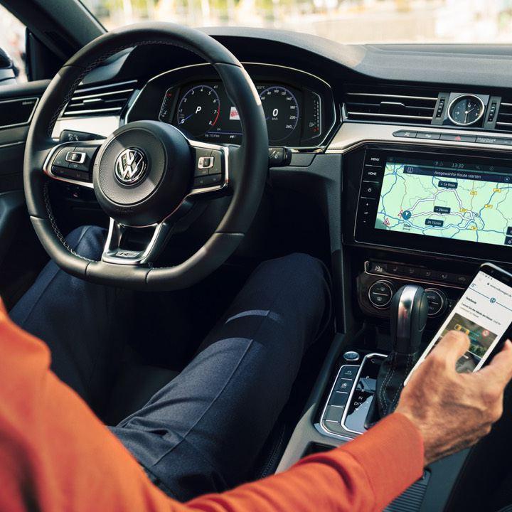 Hombre al volante con un móvil en la mano buscando talleres Volkswagen