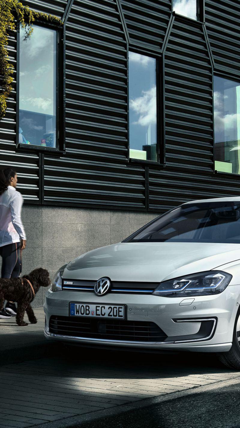 Volkswagen e-Golf blanco aparcadp en la ciudad mientras una mujer joven pasea a un perro por la acera