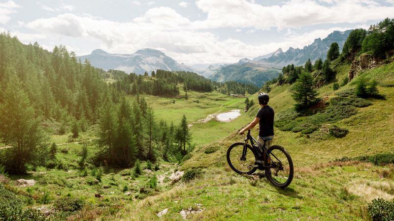 Hombre joven en bicicleta mirando un paisaje de montaña desde la altura