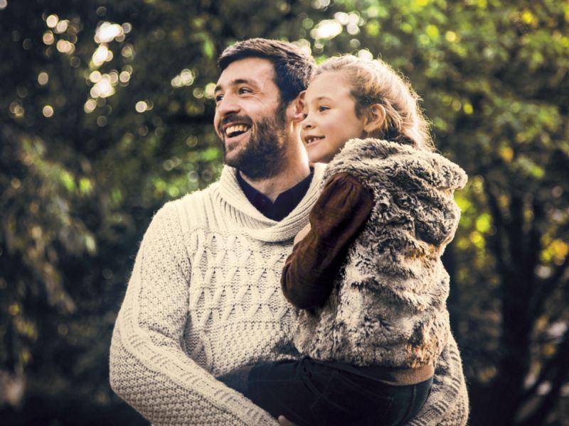 Padre con hija en brazos delante de unos árboles y mirando en la misma dirección