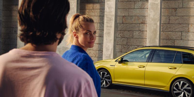 Chica mirando a la cámara detrás de un chico de espalda y al fondo un Volkswagen amarillo aparcado