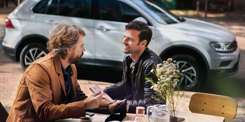 hombres reunidos en un cafe con volkswagen de fondo