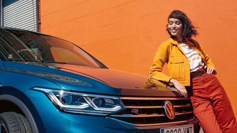 Chica sonriente con una cazadora amarilla apoyada sobre el capó de un T-Roc R azul