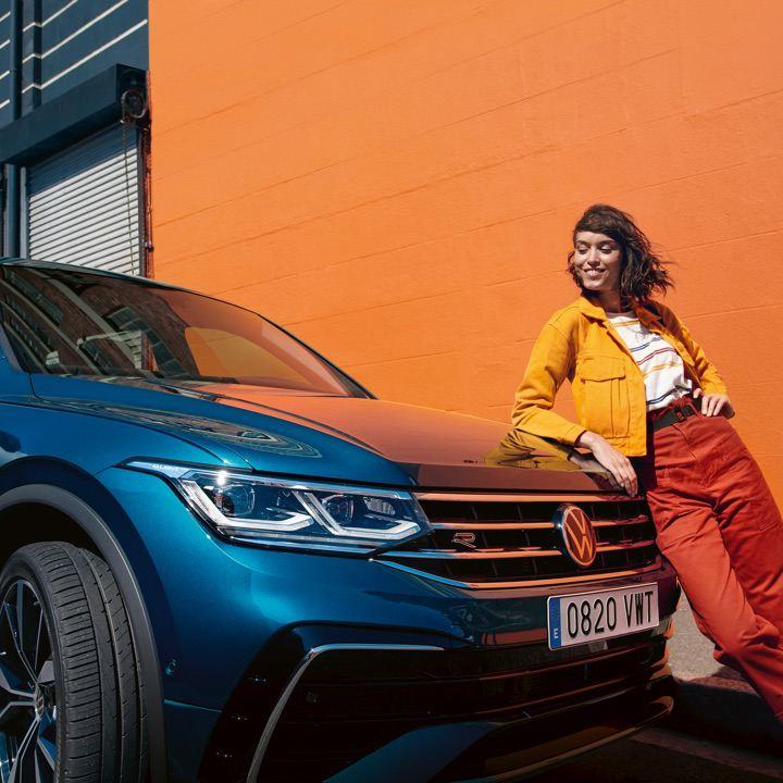 Chica con chaqueta amarilla delante de un Volkswagen Tiguan azul aparcado frente a un muro naranja