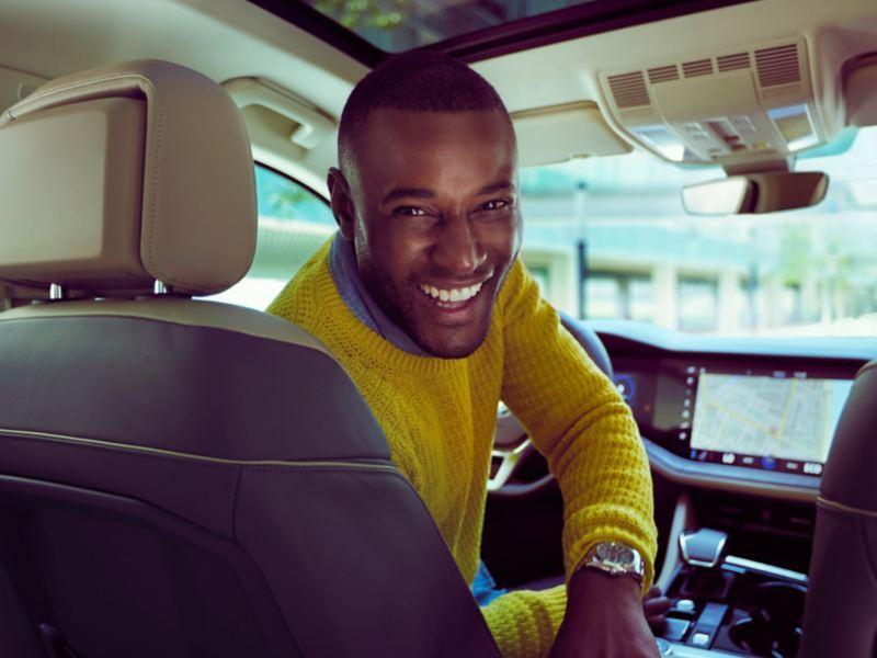 Chico sonriente mirando a la cámara sentado en el asiendo de conductor de un Volkswagen