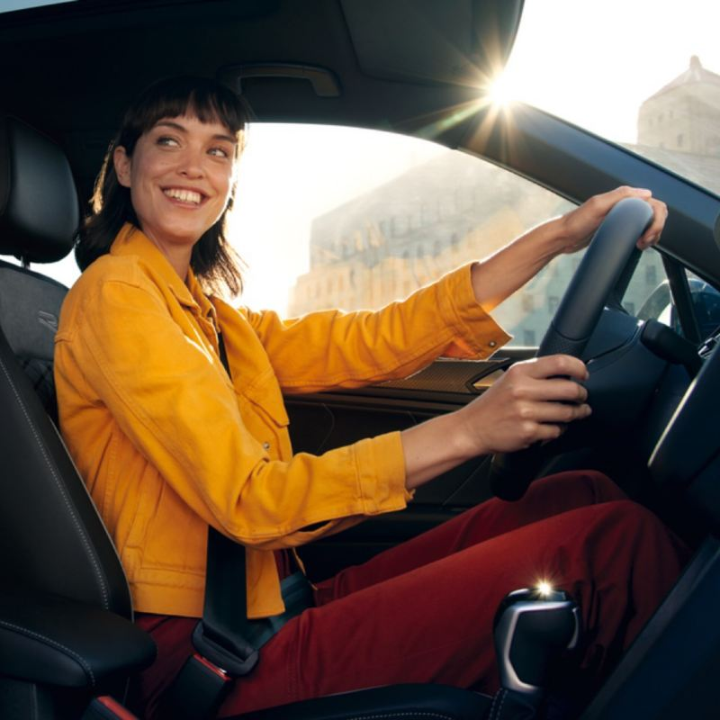 Chica sonriente con una cazadora amarilla conduciendo un Volkswagen
