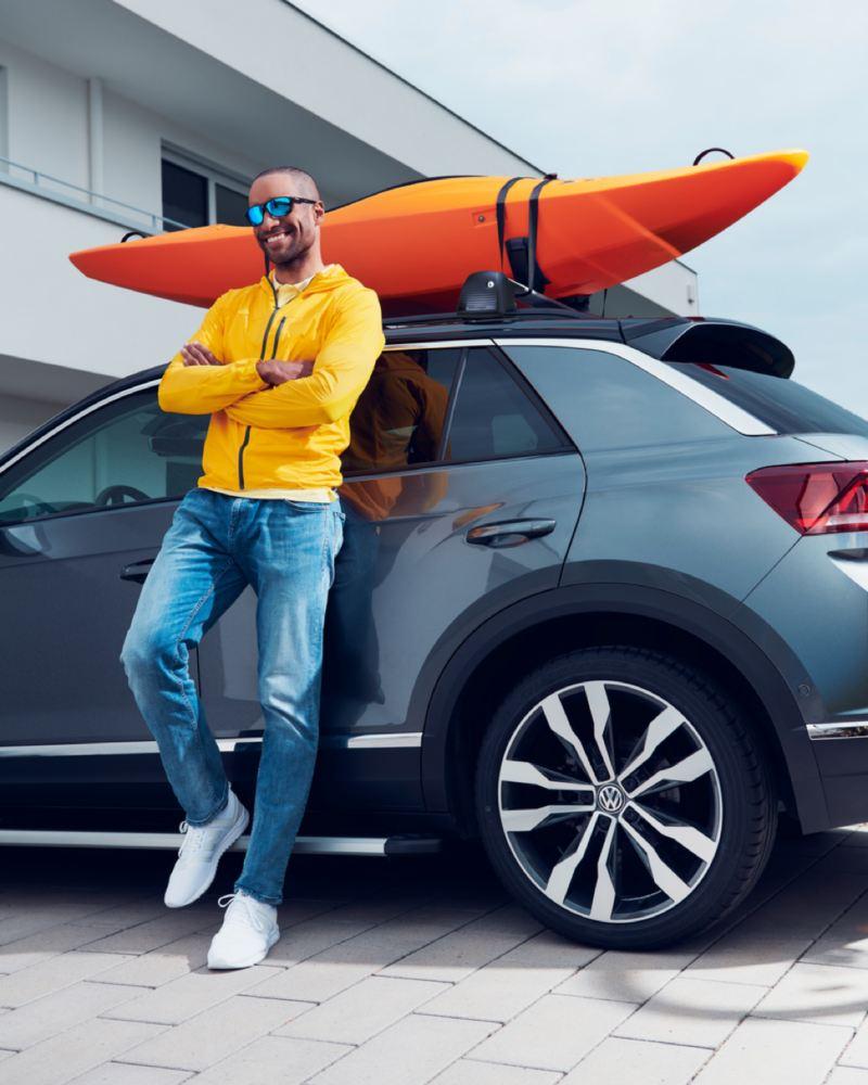 Chico con una cazadora amarilla y los brazos cruzados frente a un Volkswagen con un kayak en el techo