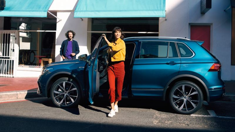 Pareja saliendo sonrientes de un Nuevo Volkswagen Tiguan azul aparcado en la calle