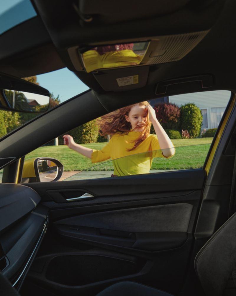 Niña pelirroja vestida de amarillo asomándose a un Volkswagen Golf 8 vista desde el interior