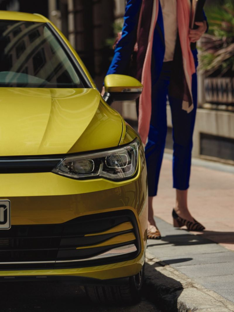 Detalle del frontal de un Volkswagen Golf 8 amarillo lima aparcado en la calle con la vista parcial de una mujer detrás