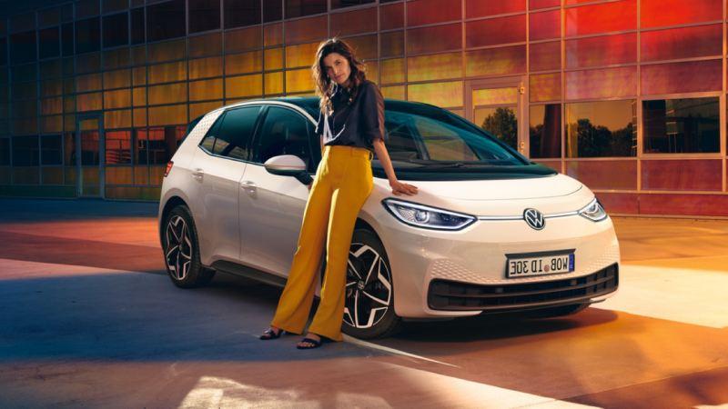 Chica apoyada en un Volkswagen ID.3 blanco aparcado frente a un edificio