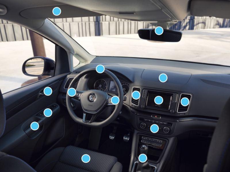 Vista del puesto de conducción y salpicadero de un Volkswagen con puntos azules indicando zonas de higienización