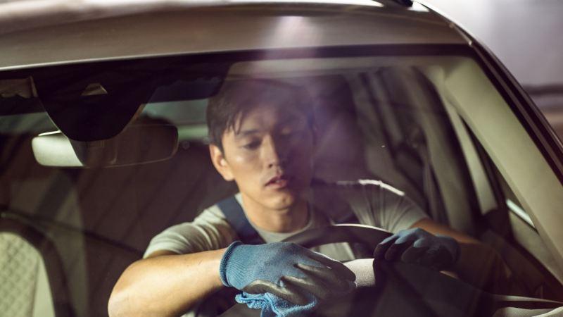 Hombre en el puesto de conducción de un Volkswagen limpiando el interior