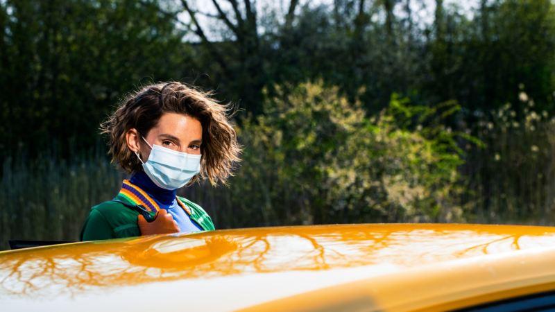 Mujer con mascarilla mirando al frente sobre la vista parcial del techo de un Volkswagen amarillo