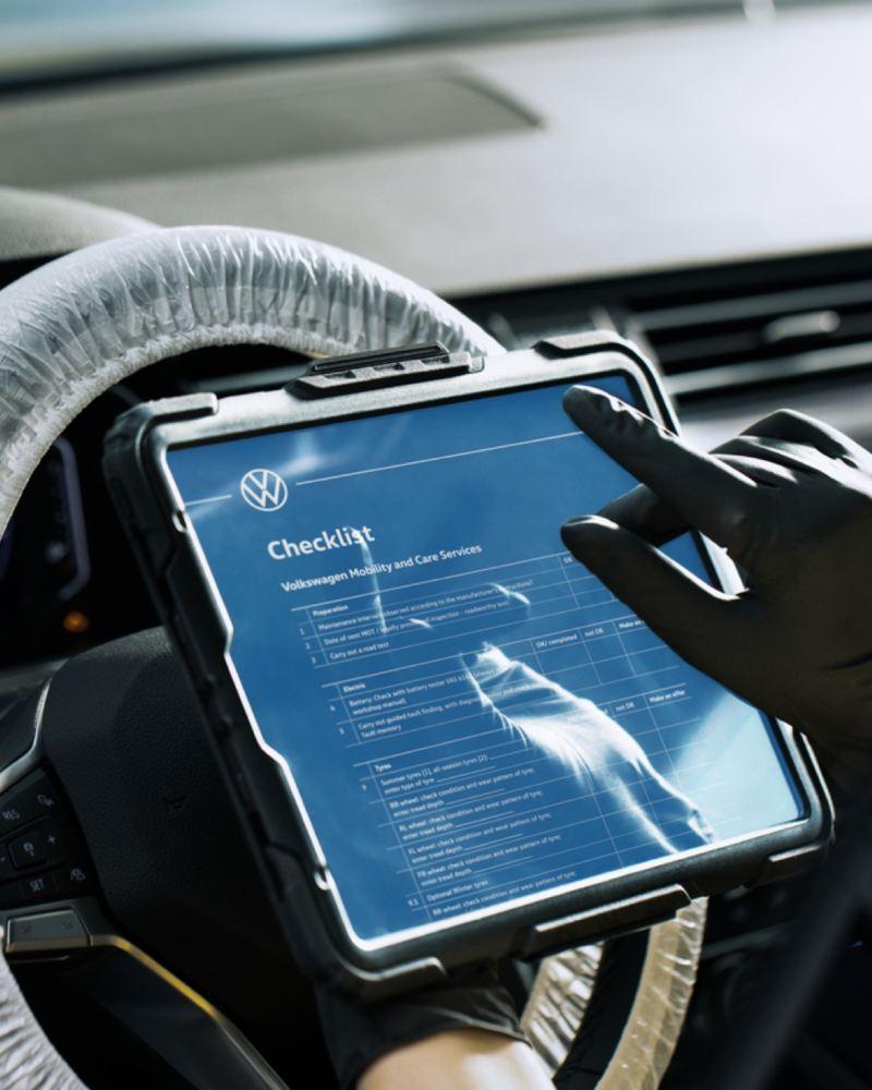 Primer plano de una mano usando una tableta apoyada en el volante con la lista de verificación de Volkswagen