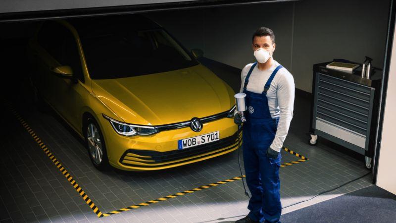 Mecánico delante de un Volkswagen Golf 8 amarillo en el taller
